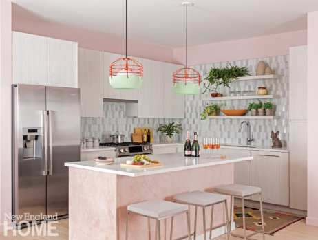 kitchen with white cabinets and a pink island. The appliances are stainless steel. The tiled backsplash is gray and white.