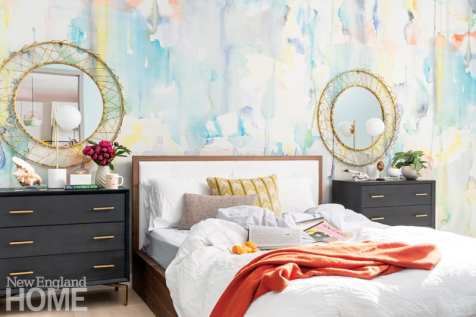 Master bedroom bed with dark wood nightstands on either side. There are round gold mirrors above the nightstands.