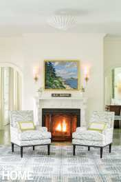 Living room with two chairs in front of a roaring fire. On the floor is a blue-and-white geometric rug.