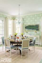 Dining rooms with patterned wallpaper in shades of pale blue, green and white. There's a glass chandelier hanging over the table.