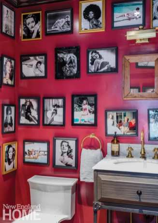 Powder room with red walls covered in black-framed photos