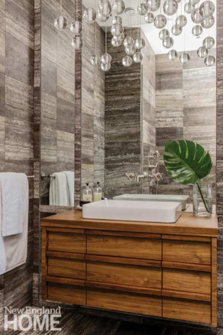 White bathroom sink on wood vanity topped with greenery in a glass vase; Julian Edelman's Back Bay Condo.