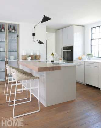 Looking into the kitchen with a view of the eat-in island and white lacquer cabinets
