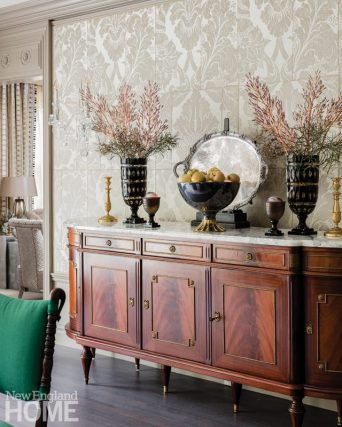 antique sideboard with a marble top. The sideboard is topped with vessels.