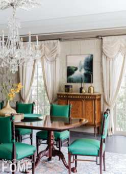 A dining room table in dark wood surrounded by dark wood chairs with Kelly-green upholstery.