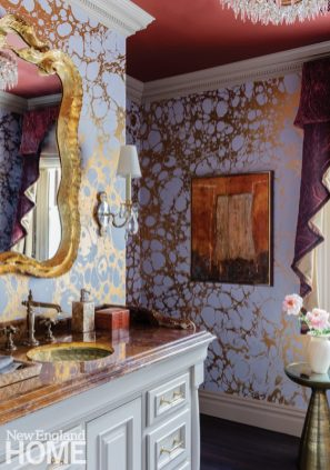 Bathroom with purple and gold wallpaper. There's a gold frame mirror above the vanity.