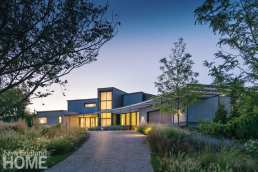 The exterior of a modern home lit up at night