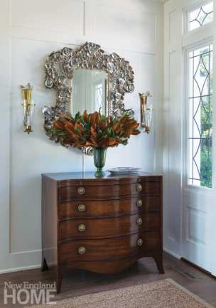 Entryway with chest topped with an arrangement of brown and green leaves