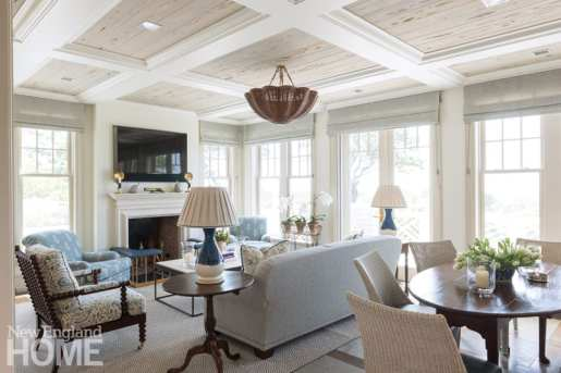 floor-to-ceiling shot of great room with furniture in shades of gray, beige and pale blue
