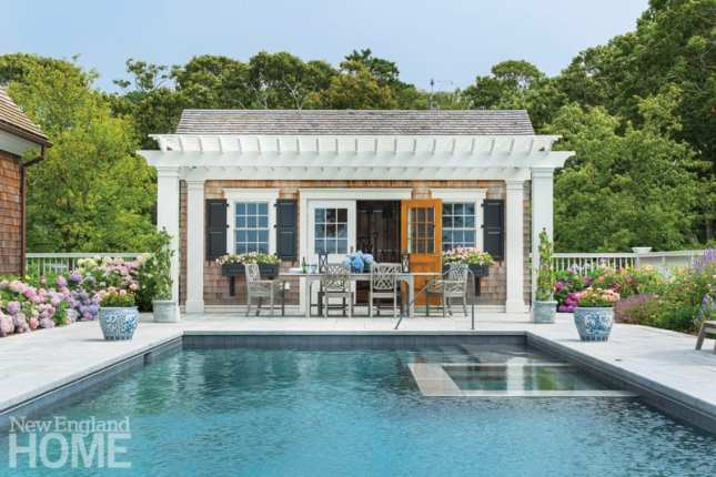 swimming pool with a pool-house style garden shed behind it and trees beyond