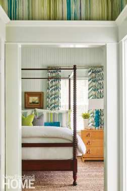 master bedroom with dark wood canopy bed and pale green shiplap walls