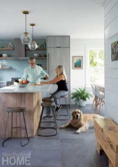 Ben and Pat Stone enjoy a glass of wine at the marble-topped reclaimed-wood island, while Franklin signals his approval of Pat's choice of gray porcelain floor tiles.