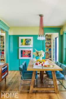 blue-green walls in the dining room with a wood table surrounded by six blue chairs