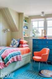 kid's bedroom with blue floors, blue bureau and orange chair