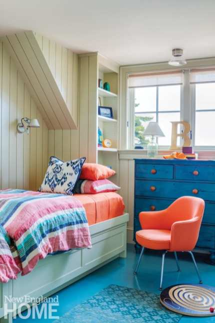 kid's bedroom with blue floors, blue bureau and orange chair