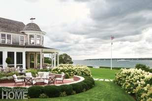 Architects Jennifer Smith and Scott Hutton sited the house to take advantage of water views and relied on traditional New England materials. They created spaces that are both outward focused and intimate—from porches and patios to tiered-level lawns. The window trim echoes the interior accent red, which was mixed to match the client's favorite lipstick and nail polish color.