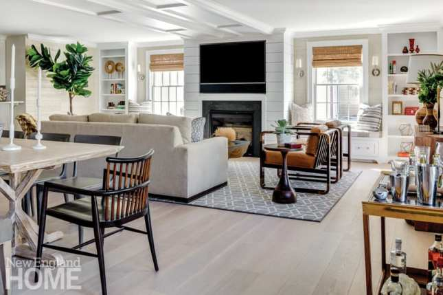 a newport vacation home's great room with sitting area, bar cart and dining table