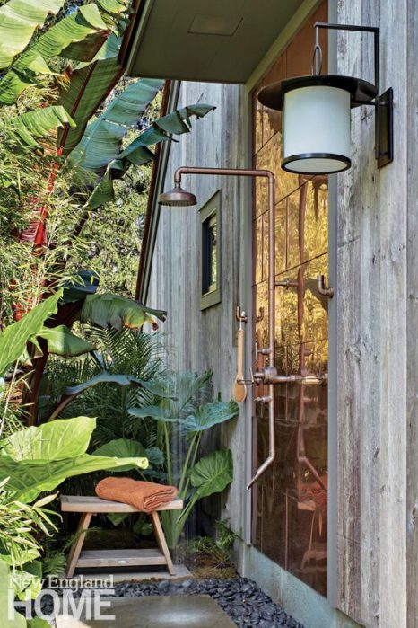 A copper wall on the outdoor shower simulates the reflective quality of a waterfall, while clusters of lush banana plants ratchet up the tropical vibe.