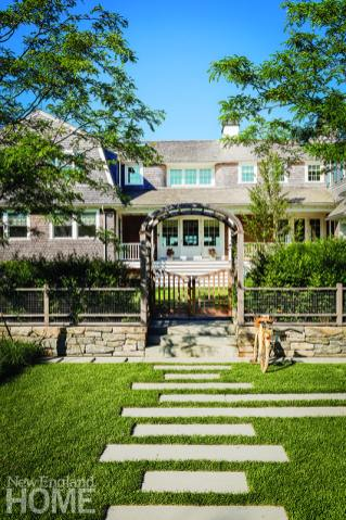 Shingle style home with arbor designed by Hutker Architects