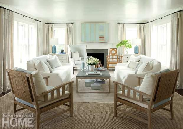 Wicker armchairs add warmth and texture to the mostly white living room. The modern abstract painting over the fireplace camouflages the television.