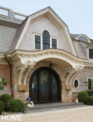 The statement-making—and welcoming—front entrance has a mahogany arched door with custom brackets and rafters for a trellised look; Reck added wrought-iron detailing to give it an Old World feel. Above, in keeping with the grand Shingle-style architecture, a widow's walk evokes a bygone era.