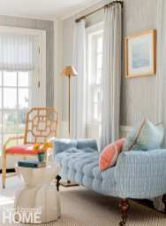 Living room with a blue and white couch and coral chair