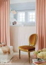 A built-in daybed in a child's bedroom was outfitted in pale pink; curtains reveal a play space below.