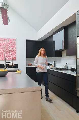 Homeowner and interior designer Emily Fuhrman approaches the cooking counter, which is clad in gray- and green-veined marble.