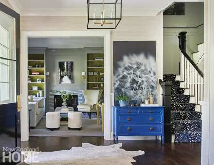 Contemporary entryway with blue dresser.