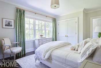 Guest bedroom with white bedding and green and white drapery.