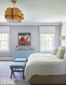 Main bedroom with gray walls and large gold light fixture.