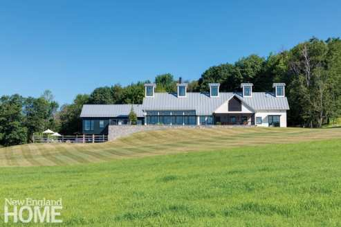Recalling a New England dairy barn, a long white block houses the living, dining, and kitchen areas.