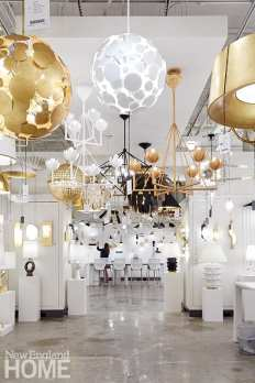 A minimalist background lets the fixtures shine at Circa Lighting's new Boston showroom. Designer Julie Neill's Luna chandeliers in both matte white and gold are seen in the foreground.