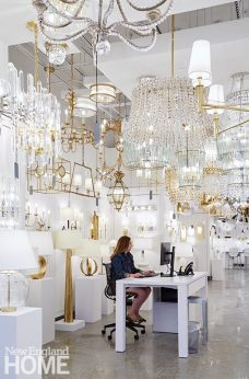 Gold and crystal chandeliers, sconces, and table lamps create a glamorous workspace for the expert lighting team.