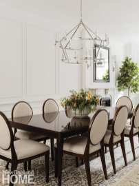 A dining table by Hickory Chair, set under Visual Comfort's Darlana chandelier, is poised for elegant dinner parties.