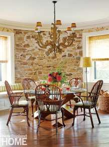 A mix of styles and eras come together in the breakfast room, where eighteenth-century Windsor chairs surround a more contemporary geometric table base, and a Paul Ferrante chandelier hovers above.