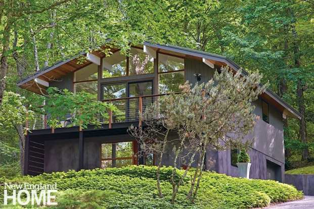 "The upper level's vertical red-cedar siding and the lower level's stucco are painted a warm, rich gray. ""It was on my wish list to have property that didn't need to be mowed,"" says the homeowner about the pachysandra, ferns, and trees that cover the half-acre lot."