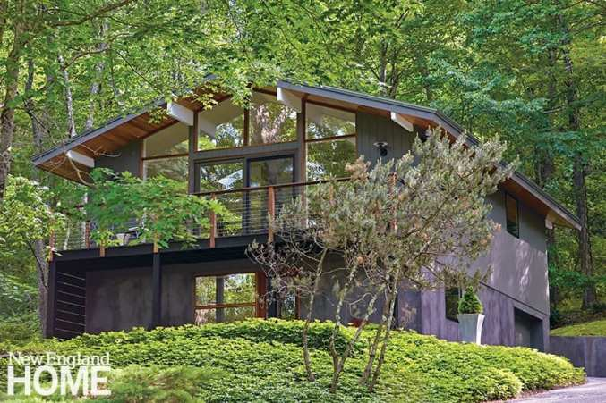 """The upper level's vertical red-cedar siding and the lower level's stucco are painted a warm, rich gray. """"It was on my wish list to have property that didn't need to be mowed,"""" says the homeowner about the pachysandra, ferns, and trees that cover the half-acre lot."""