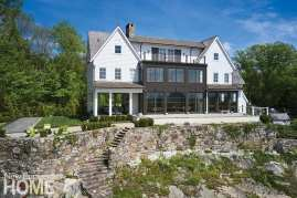 The couple chose a warm, dark tone for the wall of windows along the back elevation to complement the modern farmhouse style; steep grading here meets a stone retaining wall original to the pre-existing house, which was taken down.