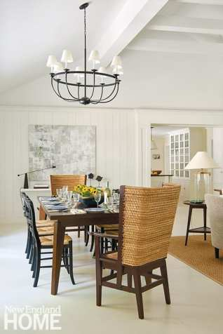 In the family room's dining area, a fixture from Shades of Light hangs above a West Elm table, Pottery Barn side chairs, and armchairs from Mainly Baskets Home; the artwork is by Mark Liebergall.