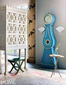 An antique Swedish Mora clock circa 1820 sits alongside a vintage Nicholas Haslam cabinet.