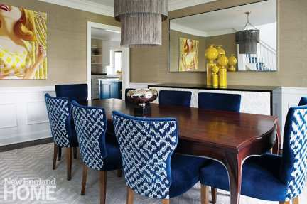 The dining room table, site of many dinner parties, was designed by Moss Design and fabricated by Old Mill Road Company. Moss Design also created the plush chairs, which are covered in upholstery from Schumacher and Kravet. The glam light is from Arteriors.