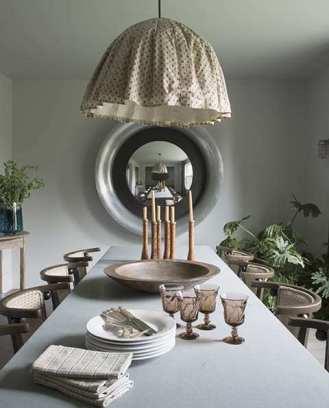 A custom Hoffmann-inspired pendant light hovers above a bluestone trestle table.