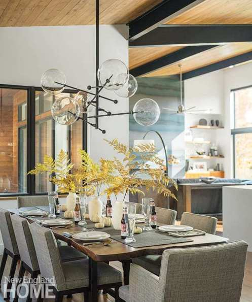 A steel-and-blown-glass chandelier helps lower the high ceiling in the dining room, which is anchored by a custom-made walnut table designed by Amber Hodgins Design.