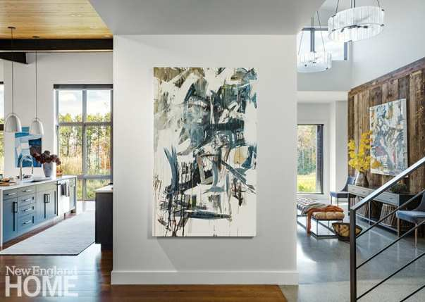 A color-splashed abstract painting by Stowe-based artist Seb Sweatman greets visitors and helps set off the kitchen from the entry.