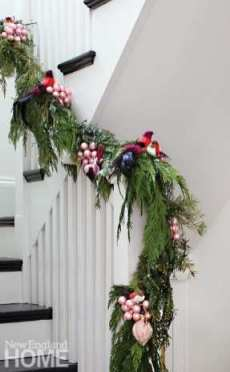 The banister is woven with a cedar-and-Douglas-fir garland accented by faux birds and clusters of matte-glass ornaments.