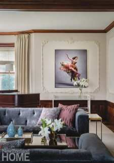 """In the living room, original plaster appliqués frame a photograph of a ballerina by Ken Browar and Deborah Ory; """"I wanted something with motion in that room,"""" says designer Tiffany LeBlanc, """"something sexy and poised to live up to the formality."""""""
