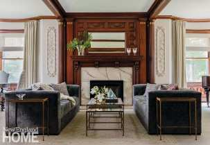 """Double blue-velvet sofas and a mirror-topped table flank the fireplace in the living room's sitting area. """"The room commanded that level of formality,"""" says LeBlanc, noting the rich, dark woodwork, the onyx surround, and plaster appliqués that display a musical theme."""