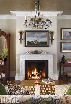 The living room's pale walls make a gallery-like backdrop for the homeowners' art collection, including the moody maritime scene by nineteenth-century artist Antonio Jacobsen that hangs above the original marble fireplace.