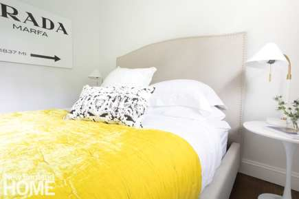 upholstered bed with white sheets and yellow comforter